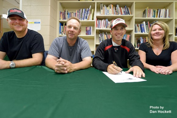 Photo by Dan Hockett West Burlington Senior Tyson Abbott (with pen), is joined by his mother Tammy Starkey - Hopkins (right), father Brian Hopkins (far left), and SCC Baseball Coach Justin Schulte (near left), as he signs to play baseball at Southeastern Community College Wednesday afternoon in West Burlington.