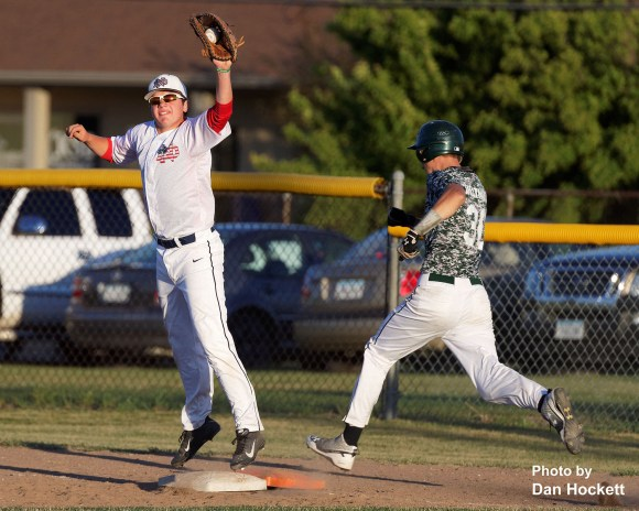 Photo by Dan Hockett A high throw brings Notre Dame First Baseman Connor Delaney off the bag just long enough to allow West Burlington's Colton Hohenthaner to be safe Thursday night in Burlington. Notre Dame defeated West Burlington, 3-1.