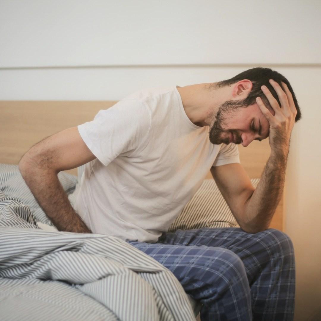 man holding head, in pain, experiencing vertigo, vestibular