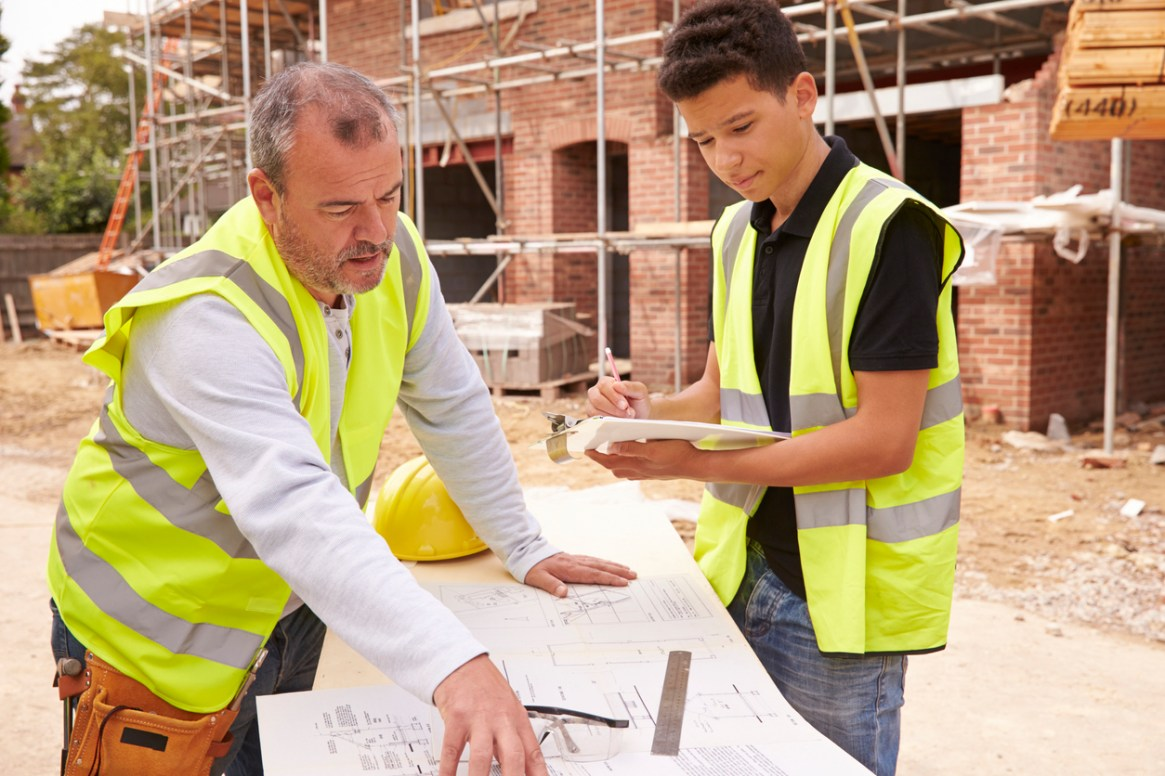 Builder On Building Site Discussing Work With Apprentice