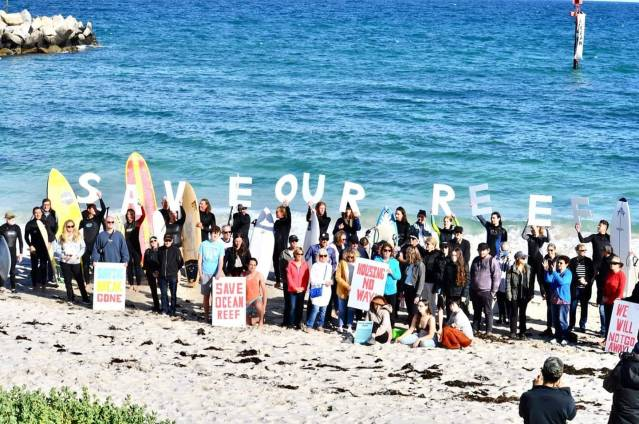 "A large group of Ocean Reef residents lined the beach at the site of the development with ""Save Our Reef"" sign."