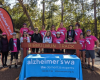 A group of hikers posing behind a Bibbulmun Track and Alzheimer's WA sign in the forrest.