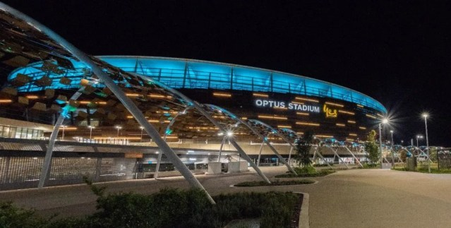 Optus Stadium at night lit up in the colour teal.