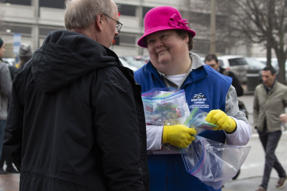 A woman in a pink hat and blue vest hands out baggies to a man in a black jacket.