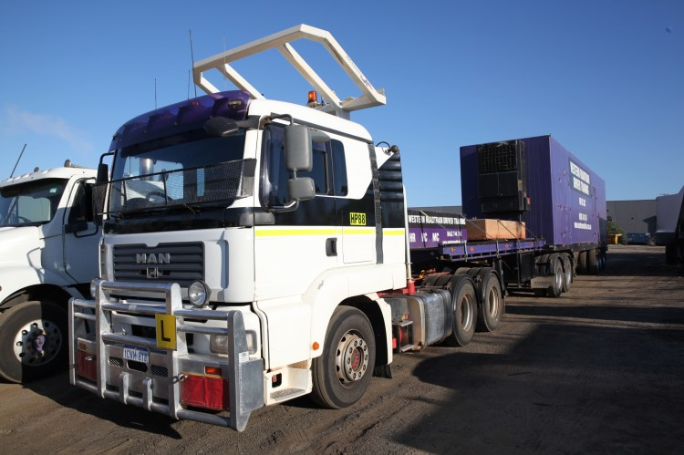 A Western Roadtrain Multi-Combination vehicle. This features the body of the truck plus two trailers. The branding is purple and represents Western Roadtrain, a Perth Truck Driving School.