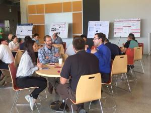 Image of attendees sitting at tables discussion posters. Students present their research and network with professional researchers at poster session