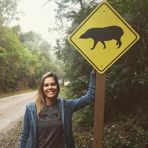 Fernanda Abra with Tapir crossing sign in Brazilian forest