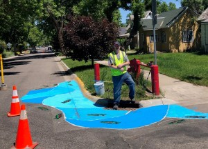 Volunteer poses with fish mural painted on Bozeman street as part of traffic calming project