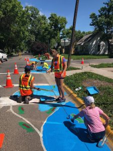 Volunteers paint traffic calming murals along residential street.