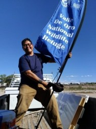 Nate Begay outside with flag that reads Valle de Oro National Wildlife Refuge
