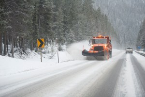 snow plow drives on snowy 2 lane highway through forest