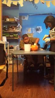 Xzavier Davis-Bilbo carves a pumpkin with sister Aurie Parris.