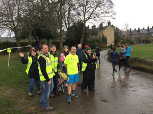 Parkrun volunteers cheer the runners round on their first lap