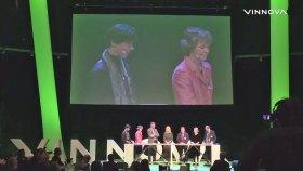 En scen med paneldeltagare och ovanför dom en stor projektorbild med närbild på panelen