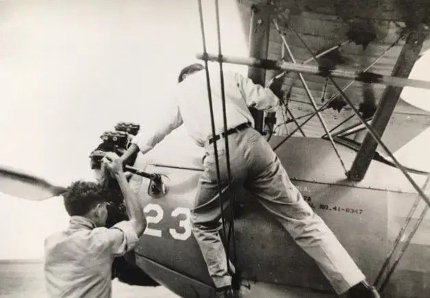 Two men crank the engine on a PT 17A at Ponca City, 1943