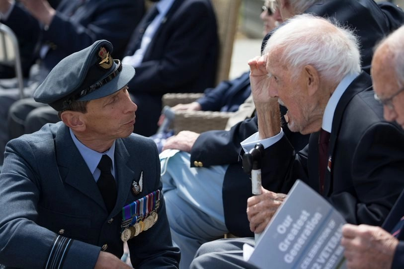 """Squadron Leader Carl Rich kneels down to speak to RAF Veteran Bill Needham at """"Our Greatest Generation,"""" an Age Cymru Dyfed event commemorating the 77th anniversary of D-Day. June 6th, 2021."""