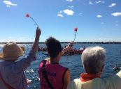Sally, a dragonboating friend, and Sharon wave carnations to participating teams, before tossing them on the water, in memory... and with much respect.