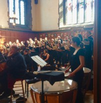 Hart House Singers: warm up with conductor David Arnot-Johnston and guest instrumentalists has started when we arrive. (Sally is just in front of nice tympanist's face.)