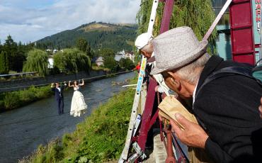 Wedding couple on a steal line over a river