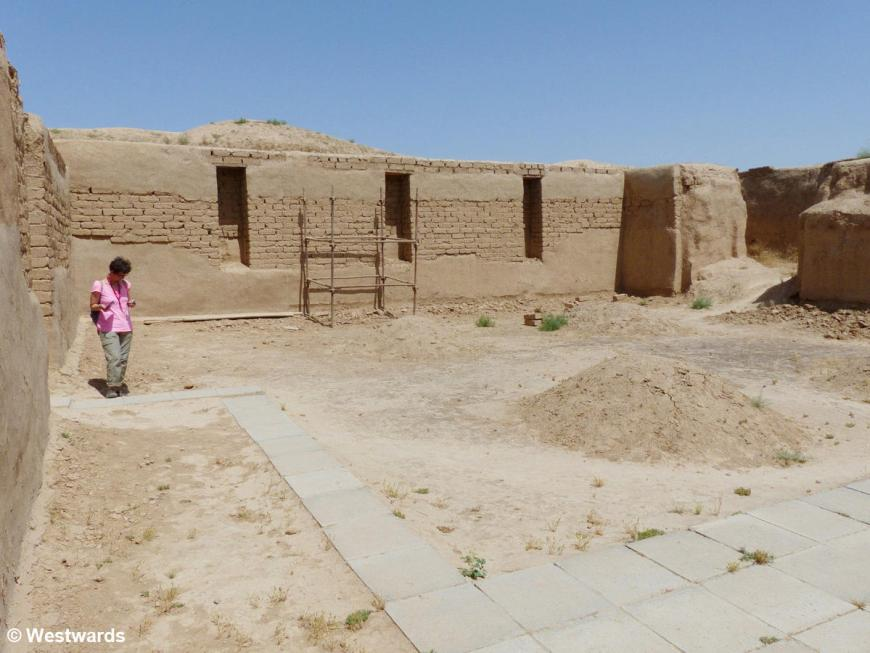 Woman in unbaked bric courtyard, Nisa