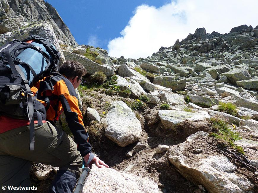 Woman scrampling on a steep hiking path with large backpack