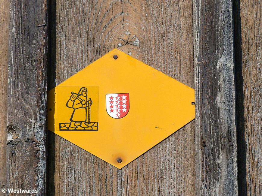hiking sign with pilgrim and valais coat of arms