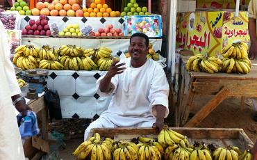 Sudanese man in white galabya selling bananas
