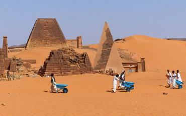 Worker with blue wheelbarows in the desert between pyramids