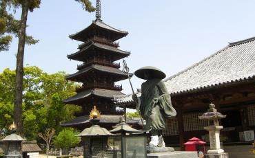 Statue of Kobo Daishi and pagoda in front of a tempel building