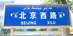 Street sign in Hotan with Chinese, Arabic and English letters