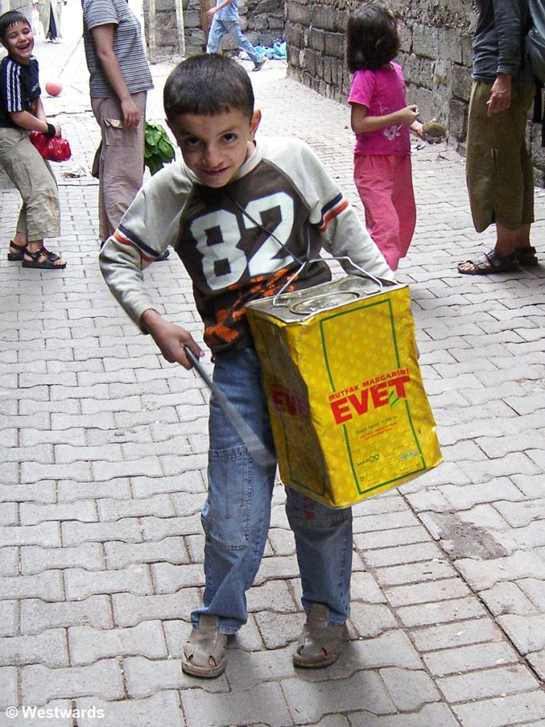 Boy with metal canister as drum during Ramadan in Diyarbakir / Anatolia