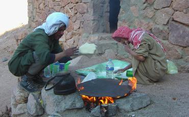 Two bedouins baking bread