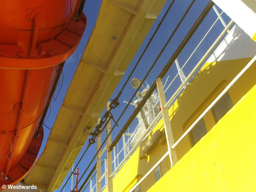 Yellow walls, red rescue boat, blue sky on the Navimag Ferry