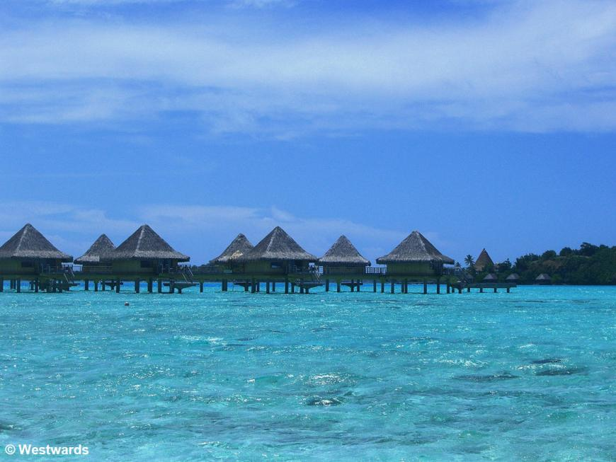 Hotel bungalows on stilts over light blue lagoon at Bora Bora Hotel Intercontinental