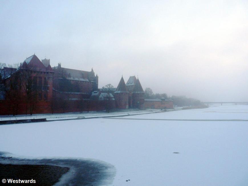 Malbork castle in snow and fog