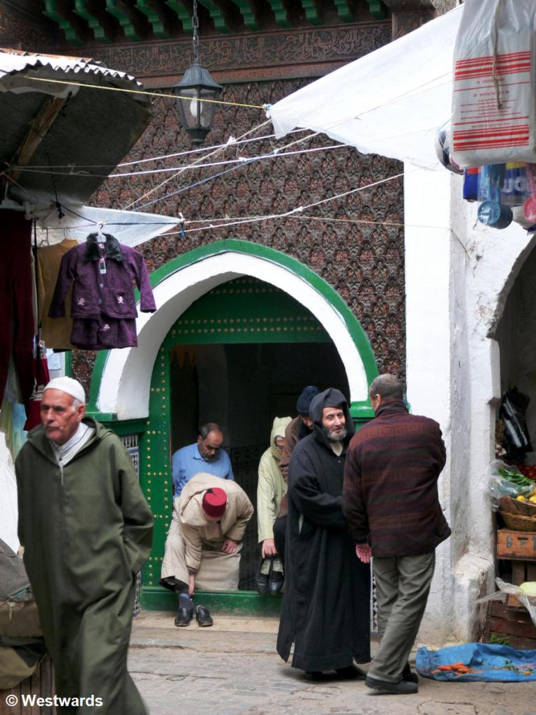 men in warm coats coming out of a mosque mosque in Tetouan Medina