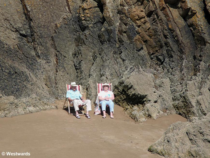 elderly couple in beach chairs with cliffs