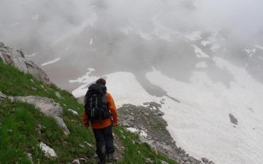 Hiker in an orange jacket on a foggy mountain path