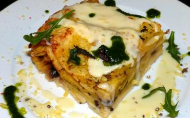 A chunk of potatoe lasagne with spinach