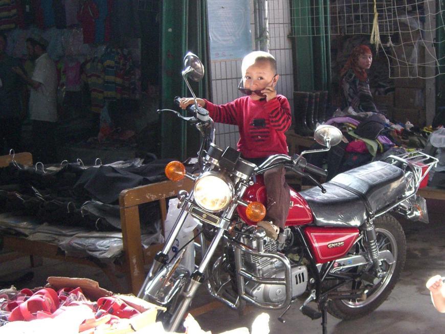 Uighur boy on a motor cycle