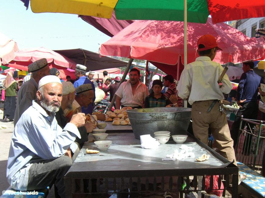 Uighur man eating bread and soup at a market food stall