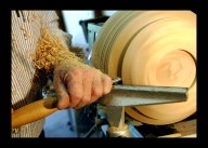 Wood shavings pile up as bowl maker Wes Kolkmeier uses a 1/2-inch spindle gouge to finish the bottom of a bowl.