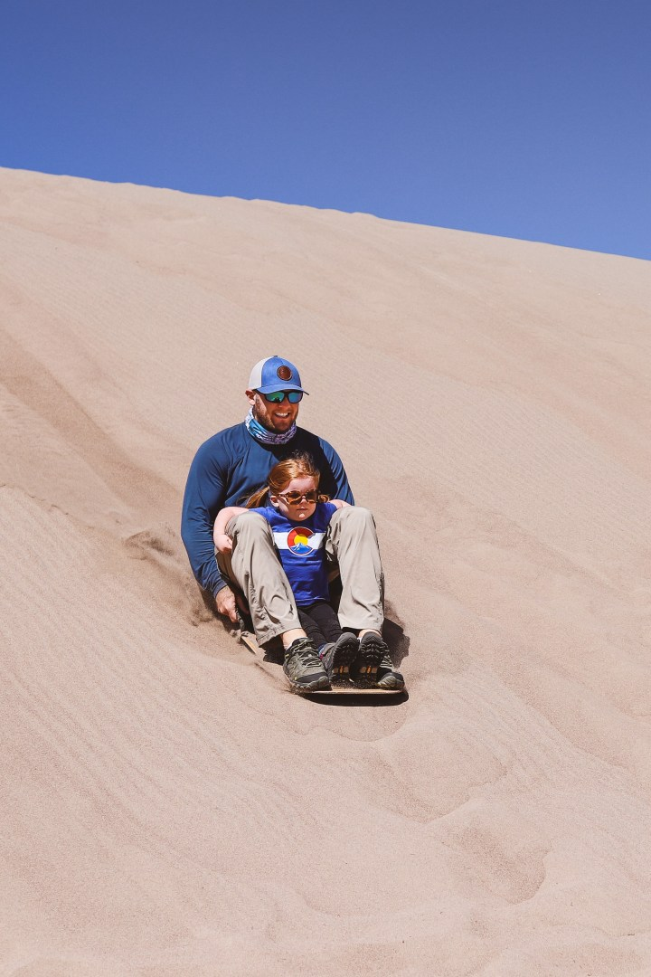 Man and little girl riding a sand board in Great Sand Dunes National Park and Preserve, Colorado