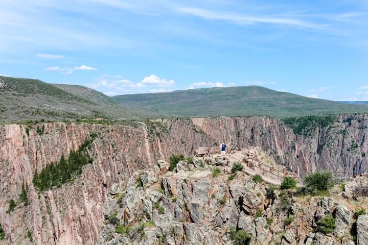 Man and baby far away at Black Canyon of the Gunnison National Park, rocky cliffs, craggy spires, Colorado