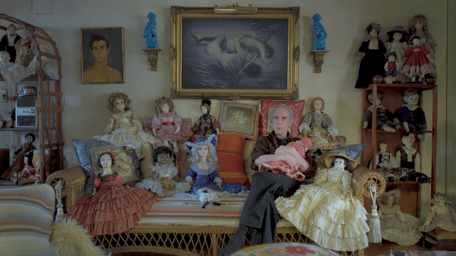 Adrian sits amongst his dolls in P.S Burn This Letter Please