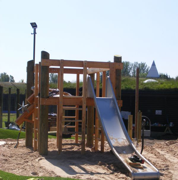 Sand underneath timber square climbing frame with metal slide