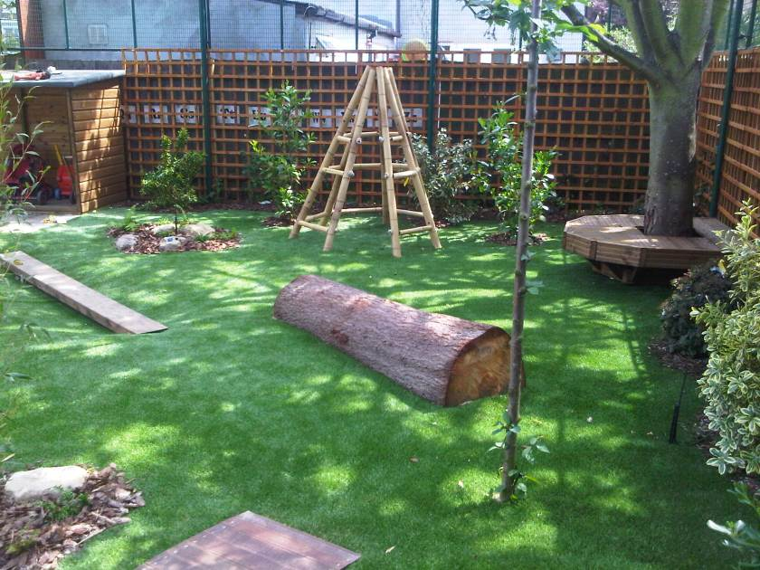 green fake grass with wooden tree trunk for climbing