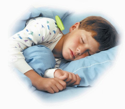 Photo of young boy asleep in bed with a Wet-Stop 3+ alarm clipped to the shoulder of his pajamas.