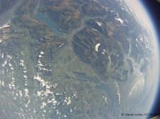 """24782.4 m ü. M., Temperatur nicht übermittelt: Blick den Alpen entlang, """"Erdkrümmung"""" durch Weitwinkelobjektiv"""