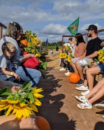 Wewa Films | People at a u-pick farm holding sunflowers and pumpkins